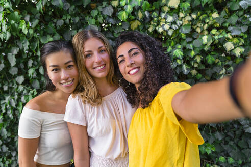 Portrait of three smiling young women taking a selfie - MGIF00659