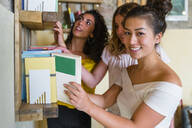 Three smiling young women at a bookshelf - MGIF00665