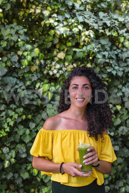 Portrait of smiling young woman holding a healthy drink - MGIF00668 - Giorgio Magini/Westend61