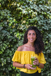 Portrait of smiling young woman holding a healthy drink - MGIF00668