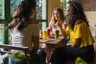 Three happy young women with smoothies meeting in a cafe - MGIF00677