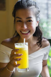 Portrait of smiling young woman drinking a smoothie - MGIF00680