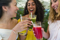 Three happy young women toasting with healthy drinks - MGIF00686