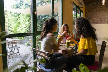 Three happy young women with smoothies meeting in a cafe - MGIF00689