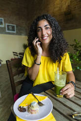 Portrait of smiling young woman on cell phone sitting at table with a smoothie - MGIF00695