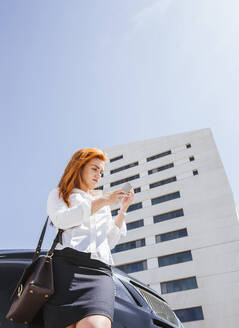 Business woman using smartphone in front of a commercial building - LJF00700