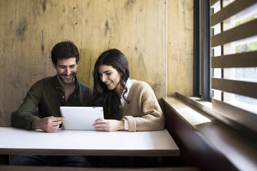 Laughing couple using digital tablet in a cafe - ABZF02426