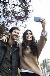 Portrait of happy couple taking selfie with mobile phone - ABZF02435