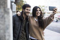 Portrait of happy couple taking selfie with mobile phone - ABZF02438