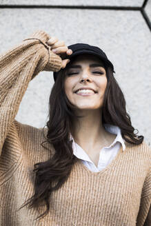 Portrait of smiling young woman wearing cap - ABZF02444