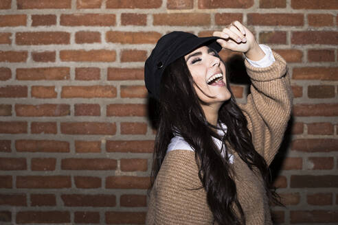 Portrait of laughing young woman wearing cap in front of brick wall - ABZF02450