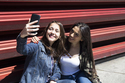 Young women sitting on ground and posing for selfie in Madrid, Spain - ABZF02495