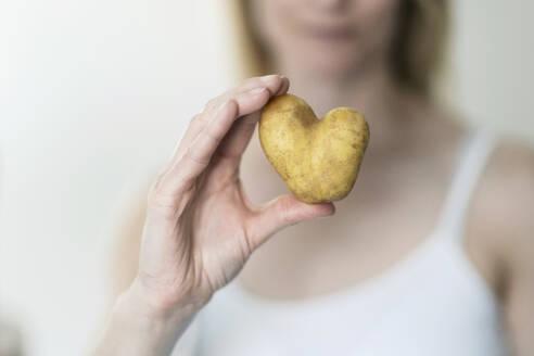 Woman's hand holding heartshaped potato - CHPF00568