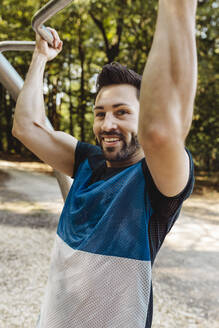Portrait of smiling man lifting himself up on a fitness trail - MFF04781