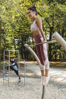 Woman lifting herself up on a fitness trail - MFF04784
