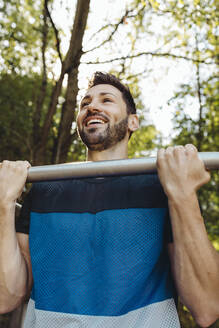 Happy man lifting himself up on a fitness trail - MFF04793