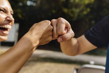 Man and laughing woman fist bumping on a fitness trail - MFF04835