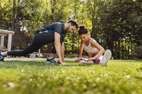 Man and woman stretching on grass near a fitness trail - MFF04841