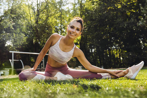 Portrait of smiling woman stretching on grass near a fitness trail - MFF04844