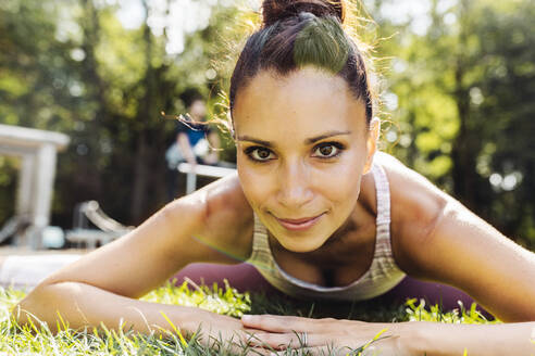 Portrait of woman stretching on grass near a fitness trail - MFF04847