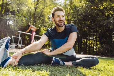 Man stretching on grass near a fitness trail - MFF04850