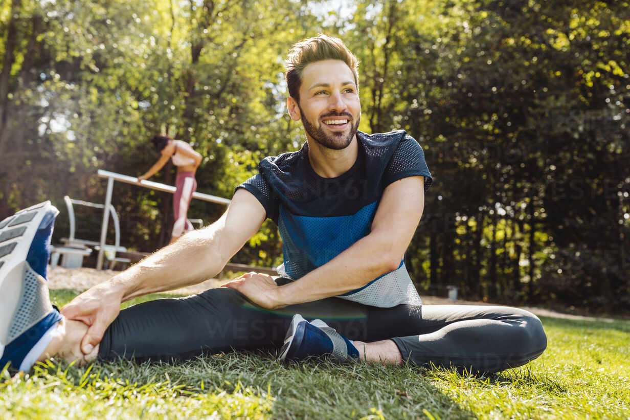 Man stretching on grass near a fitness trail - MFF04850 - Mareen Fischinger/Westend61