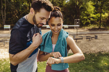 Sporty man and woman looking at a smartwatch in a park - MFF04856