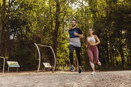 Sporty man and woman running near a fitness trail - MFF04859