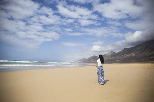 Back view of woman standing on the beach looking to the sea, Fuerteventura, Spain - ABZF02511
