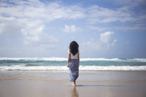 Back view of woman standing on the beach looking at the sea, Fuerteventura, Spain - ABZF02514