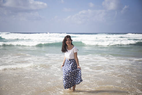 Portrait of laughing woman standing at seaside, Fuerteventura, Spain - ABZF02517