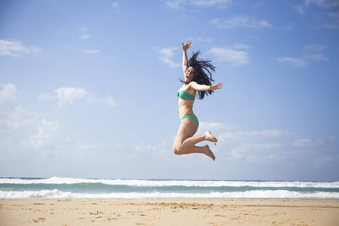 Laughing woman jumping in the air on the beach, Fuerteventura, Spain - ABZF02520