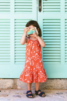 Little girl playing with wooden toy camera wearing red dress with floral design - GEMF03115
