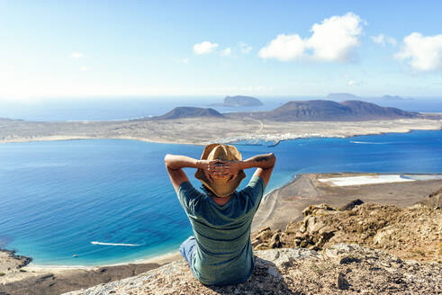 Man on viewpoint looking to La Gracioas island from Lanzarote, Canary Islands, Spain - KIJF02633