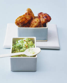 Roasted chicken wings with cucumber pineapple salsa on blue background - PPXF00258