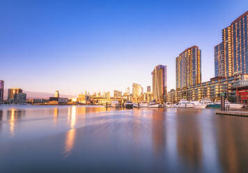 Illuminated buildings by river at Melbourne Docklands against blue sky at dusk, Victoria, Australia - SMAF01316