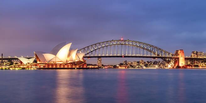 Illuminated Sydney Harbor Bridge over river against sky at dusk - SMA01325