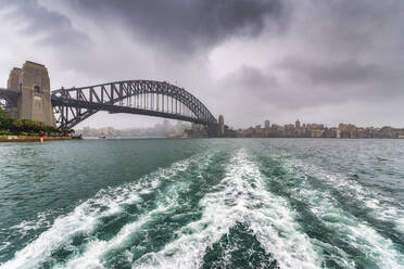Sydney Harbor Bridge over river against cloudy sky, Sydney, Australia - SMAF01331
