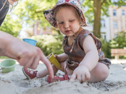Portrait of little girl with her mother in sandbox on playground - LAF02353