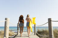 Rear view of young women with yellow airbed and sunshade walking to the beach - JPTF00250