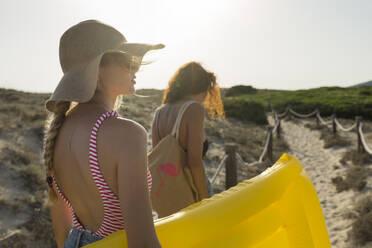 Young women walking to the beach - JPTF00253