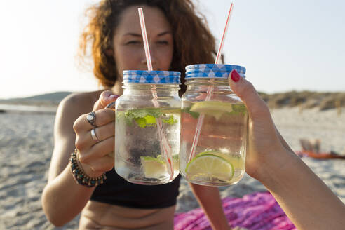 Two glasses with water, lime and mint, friends toasting at the beach - JPTF00265