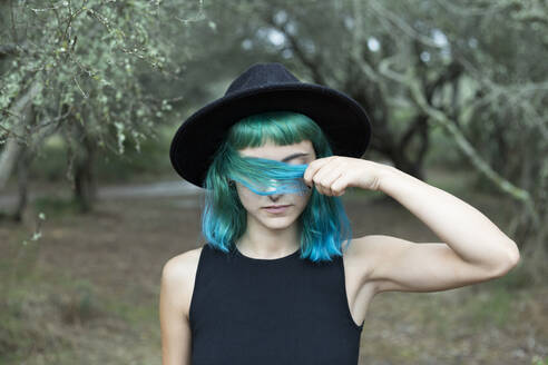 Portrait of young woman with dyed blue and green hair wearing black hat on rainy day - JPTF00274