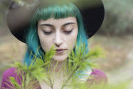Portrait of young woman with dyed blue and green hair and nose piercing in nature - JPTF00280