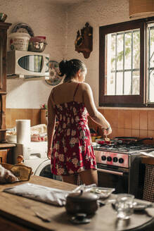 Rear view of woman cooking in kitchen using a pan - ACPF00587