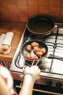 Close-up of a woman cooking croquettes in a pan - ACPF00590