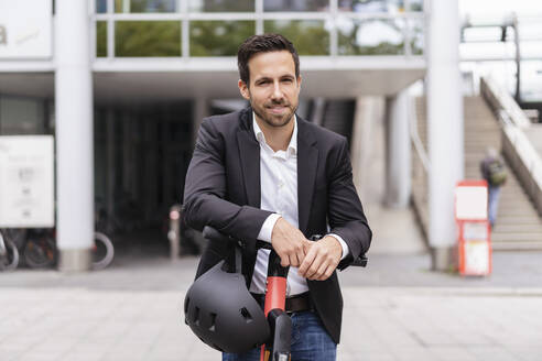 Portrait of businessman with e-scooter in the city - DIGF08066