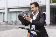 Businessman with e-scooter in the city putting on helmet - DIGF08069