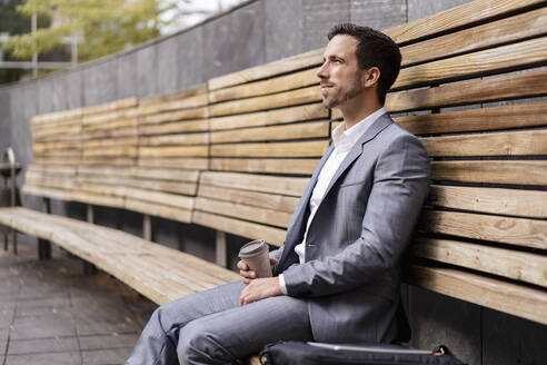 Relaxed businessman sitting on wooden bench in the city - DIGF08084