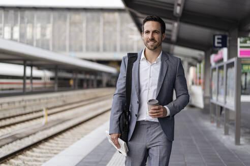 Businessman with takeaway coffee walking on station platform - DIGF08108